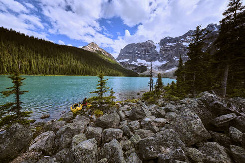 A woman is preparing to paddle across Cirque Lake in Banff Canada. - CAVF72777