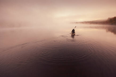 Solo paddling on a misty pond at sunrise. - CAVF72855
