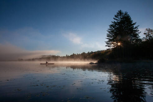 Solo paddling on a misty pond at sunrise. - CAVF72870