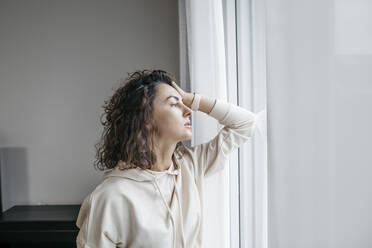 Portrait of pensive woman looking out of window - KMKF01191