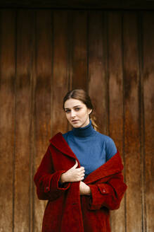 Close up portrait of woman with blue turtleneck pullover and red coat in front of a wooden door - TCEF00007