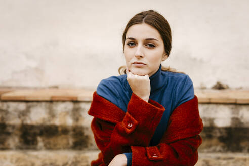Close up portrait of woman with blue turtleneck pullover and red coat, hand on chin - TCEF00010