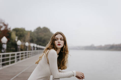Portrait of young woman wearing white dress, leaning on railing on rainy day - TCEF00019