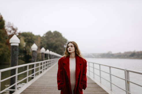 Portrait of young woman wearing red coat on a bridge during rainy day - TCEF00025