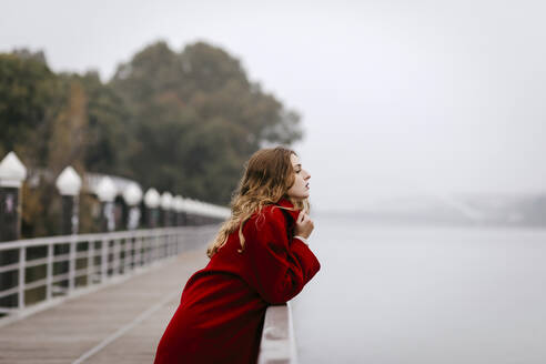 Portrait of young woman wearing red coat, leaning on railing on rainy day - TCEF00028