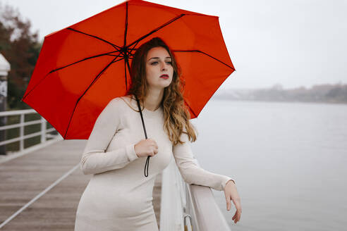 Portrait of young woman with red umbrella, leaning on railing during rainy day - TCEF00034