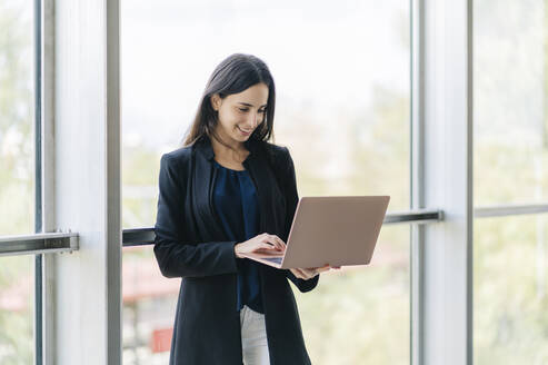 Smiling businesswoman using laptop - DGOF00017