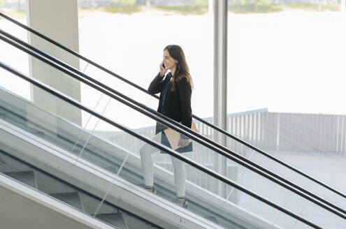Smiling businesswoman on escalator talking on the phone - DGOF00029