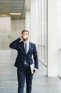 Businessman on the go drinking takeaway coffee - DGOF00053
