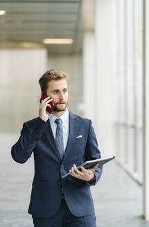 Businessman holding tablet talking on the phone - DGOF00056