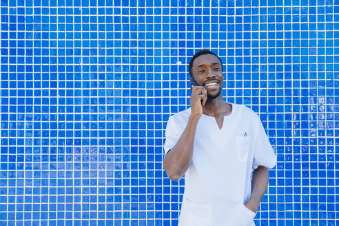 Portrait of laughing doctor on the phone standing against blue tiled wall - JCMF00344
