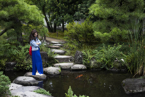 Japan, Kyoto, Woman on stepping stones in pond - ABZF02965