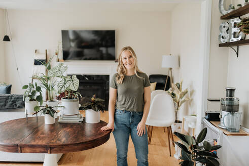 Portrait of woman in room full of house plants - ISF23650