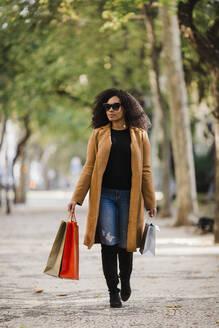 Stylish young woman walking with shopping bags on sidewalk - FSIF04535