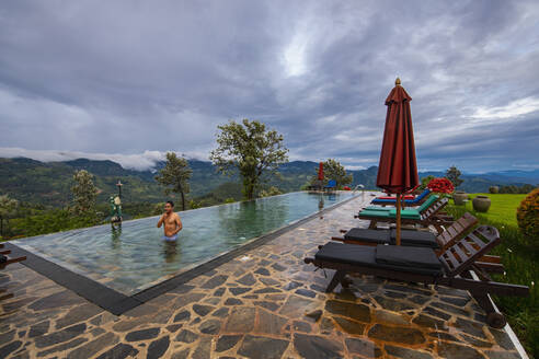Man relaxing in swimming pool on the central highlands in Sri Lanka - CAVF73214