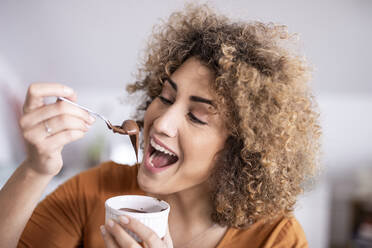 Portrait of happy woman eating chocolate spread at home - FMKF06074