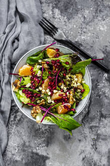 Winter salad with lettuce, tangerines, walnuts, feta and pomegranate seeds - SARF04426