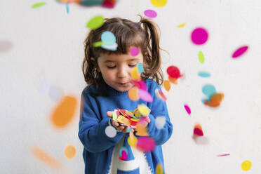 Happy little girl blowing the confetti at a party in front of a white wall - GEMF03412