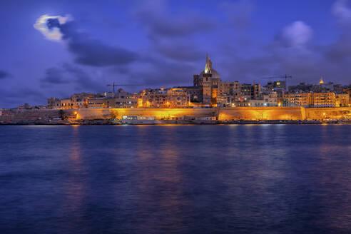 Malta, Valletta, View of city illuminated at night across water - ABOF00481