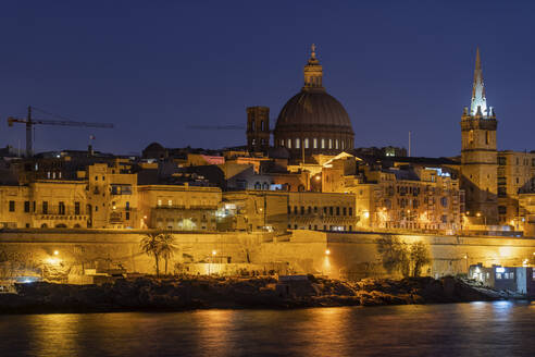 Malta, Valletta, Illuiminated city skyline across sea at night - ABOF00490