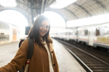 Portrait of smiling young woman at the train station - VABF02498