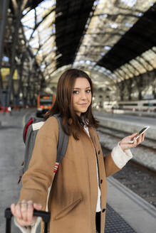 Portrait of smiling young woman holding cell phone at the train station - VABF02501