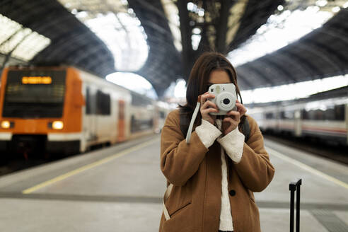 Young woman taking picture with camera at the train station - VABF02510