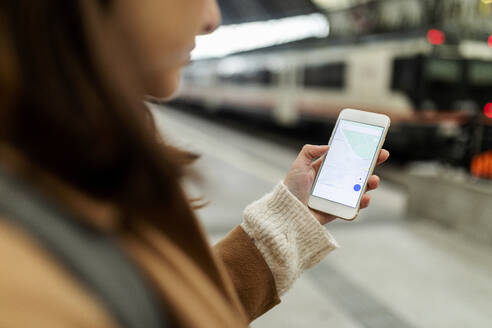 Close-up of woman using cell phone at the train station - VABF02516