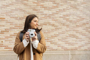 Young woman with camera in front of a brick wall looking around - VABF02522