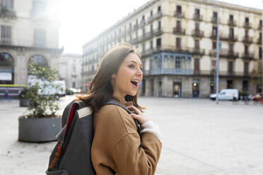 Happy young woman with backpack in the city, Barcelona, Spain - VABF02525