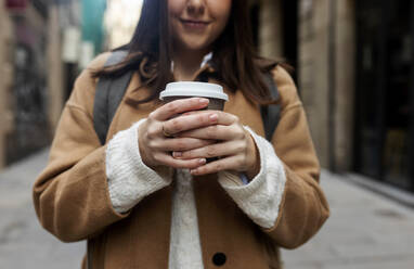 Close-up of young woman with takeaway coffee in the city, Barcelona, Spain - VABF02540