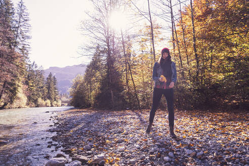 Woman wearing red woolly hat and denim jacket walking at riverside in autumn - DHEF00016