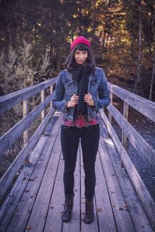 Woman wearing red woolly hat and denim jacket on a bridge in autumn - DHEF00031
