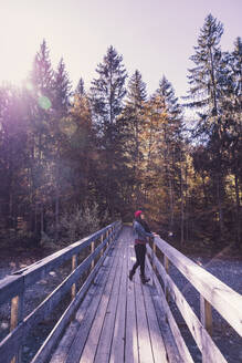 Woman wearing red woolly hat and denim jacket on a bridge in autumn - DHEF00037