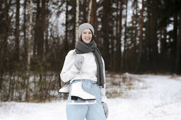 Portrait of happy woman with ice skates in winter - EYAF00811