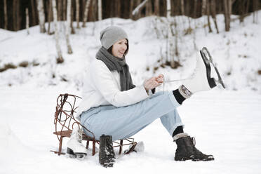 Portrait of smiling woman putting on ice skates on snow field - EYAF00814