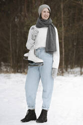 Portrait of smiling woman with ice skates in winter - EYAF00817
