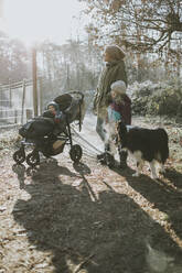 Mother with daughters and border collie during forest walk in autumn - DWF00532