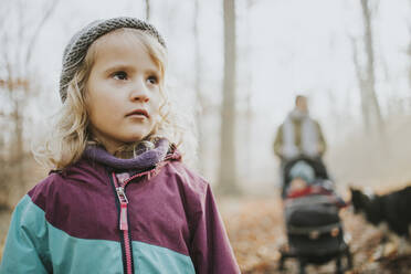 Blond girl with her mother, sister and border collie in the background during forest walk in autumn - DWF00550