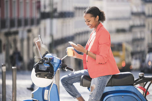 Smiling young woman using cell phone on motor scooter in the city, Lisbon, Portugal - UUF20089