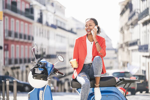 Laughing young woman with motor scooter talking on the phone in the city, Lisbon, Portugal - UUF20098