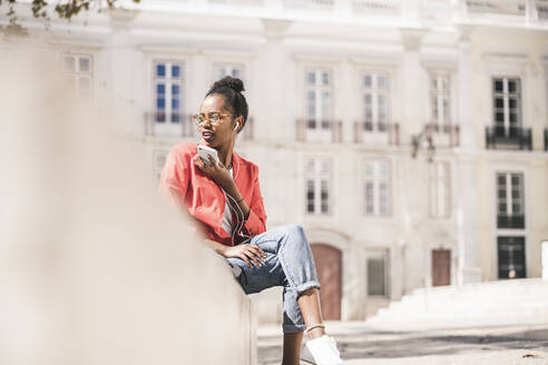 Young woman with earphones and smartphone in the city, Lisbon, Portugal - UUF20128