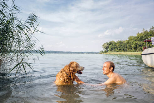 Young man with his Golden Retriever in a lake - MAMF01035