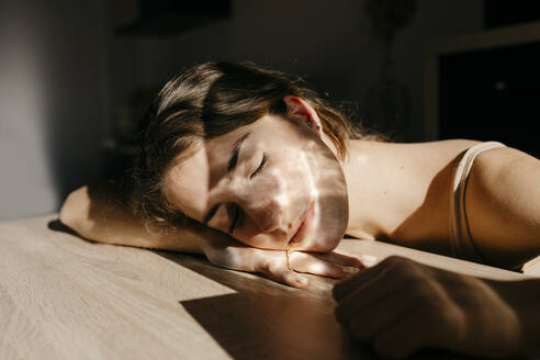Portrait of young woman with eyes closed leaning on wooden table at sunlight - TCEF00035