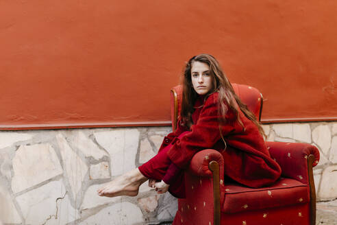 Portrait of barefoot young woman waering red jacket sitting on lounge chair - TCEF00044
