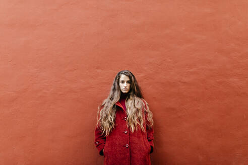 Portrait of selfconfident young woman with long brown hair wearing red jacket leaning against red wall - TCEF00047