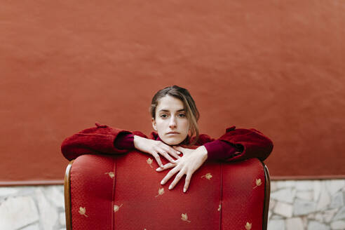 Portrait of serious young woman eaning on back rest of red lounge chair - TCEF00050