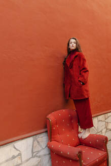 Portrait of young woman dressed in red standing barefoot on armrest of red lounge chair leaning on red wall - TCEF00053