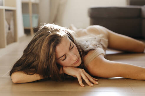 Young woman relaxing on floor at home - TCEF00059