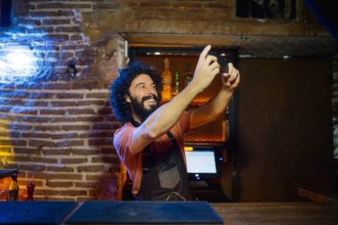 Young man, working in bar, taking selfie with his smartphone - CJMF00237